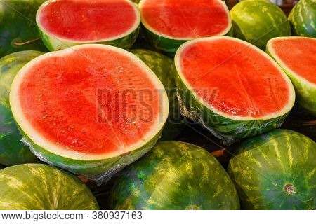 Watermelon Cut Into Halves On The Counter Of The Village Fair. Pile Of Green Watermelons, A Market B