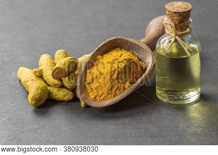 Glass Bottle Of Essential Oil Turmeric, Turmeric Powder In Wooden Spoon And Root On Rustic Backgroun
