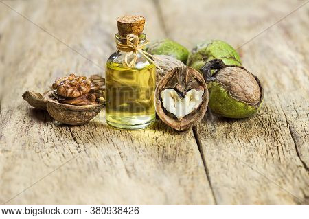 Walnut Oil In Glass Of Bottle, Whole Big Peeled Walnut Kernel With Thin Shell On Wooden Background.