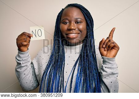 Young african american plus size woman with braids holding reminder paper with no message surprised with an idea or question pointing finger with happy face, number one