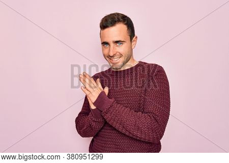 Young handsome man with blue eyes wearing casual sweater standing over pink background clapping and applauding happy and joyful, smiling proud hands together