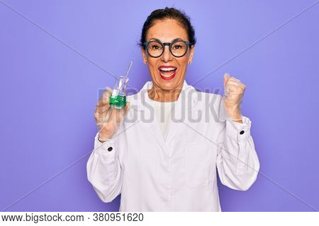 Middle age senior scientist woman wearing laboratory coat holding research test tube screaming proud and celebrating victory and success very excited, cheering emotion