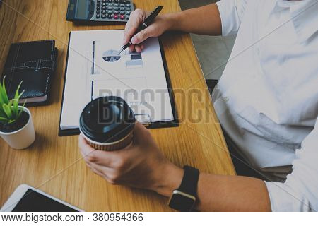 Businessman Working With Income Statement Document On The Wood Table.business Concept.