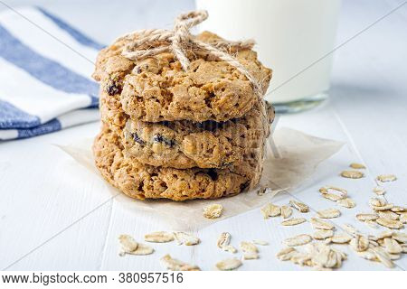 Homemade Oatmeal Cookies With Raisins And Chocolate And Glass Of  Milk On White Table. Healthy Snack