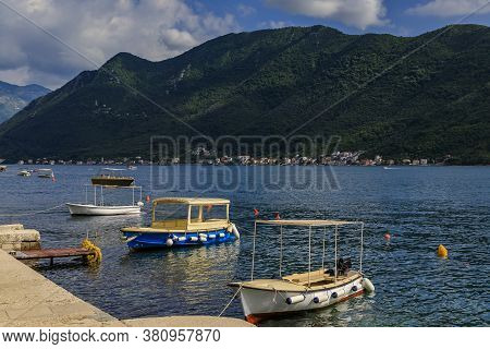 Scenic View Of Boats Docked In The Postcard Perfect Town Of Perast In Kotor Bay With Mountains In Th