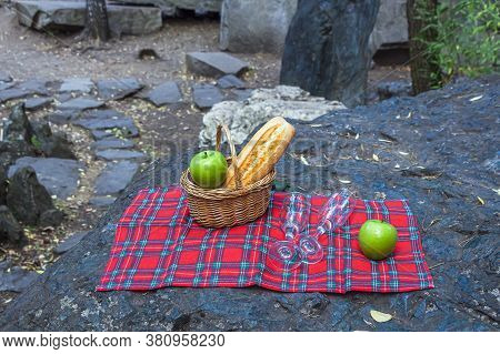 Picnic Basket With Wine Glass And Fruits On Checkered Cloth On Rocks. Romantic Still Life Of Autumn