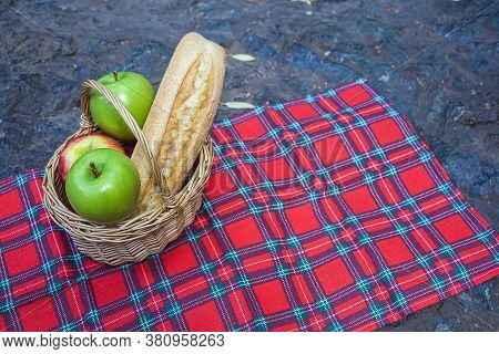 Picnic Basket With Baguette And Fruits On Checkered Cloth On Rocks. Romantic Still Life Of Autumn Or