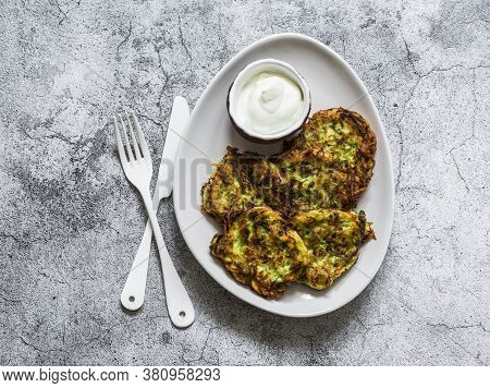 Potatoes, Zucchini, Herbs Fritters With Sour Cream Sauce On A Gray Background, Top View. Delicious B