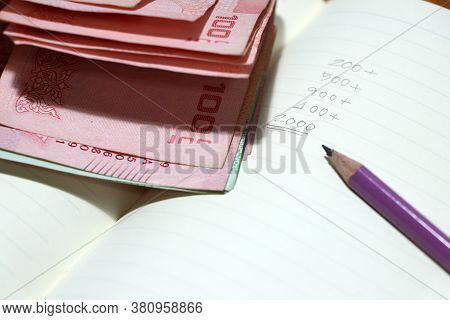Writing The Amount Of Money In The Book By Pencil With A Certain Amount Of Thai Baht. Concept Of Fin