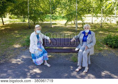 The Sad Senior Women In Social Distancing Sitting At Park. The Covid-19, Health, Safety And Pandemic
