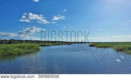 Calm, Peaceful Summer Landscape. The Blue River Flows Between Green Grassy Banks. Far Away The Fores