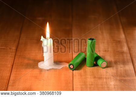 Burning Candle And Li Ion Batteries. Modern And Medieval Lighting.