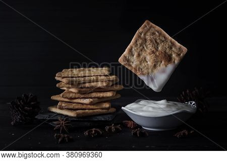 Floating Salted Cracker With Plain Yogurt, Pile Of Crackers Isolated On A Black Background