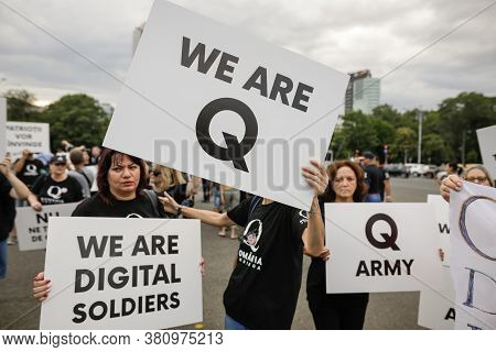 People Display Qanon Messages On Cardboards During A Political Rally.