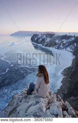 Lake Baikal At Winter. Woman Sitting On A Edge Of Cliff And Looking At Frozen Baikal Lake. Olkhon Is