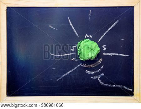 Green paper light bulb on blackboard. Corporate Social Responsibility, responsible business, eco friendly, sustainable living concept.