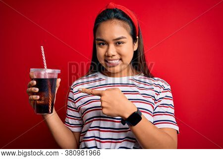 Young asian girl drinking cola fizzy refreshment using straw over isolated red background very happy pointing with hand and finger