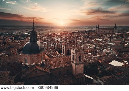 Aerial view of Toledo town skyline with historical buildings at sunset in Spain.