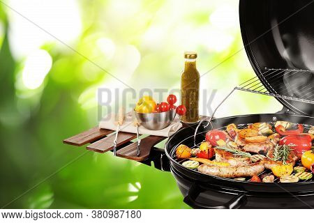 Barbecue Grill With Meat Products And Vegetables On Blurred Green Background, Closeup