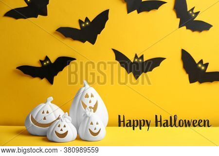 Happy Halloween Greeting Card Design. Jack-o-lantern Candle Holders And Paper Bats On Yellow Backgro