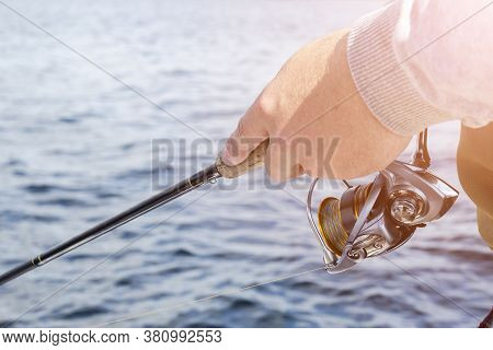 Fishing On The Lake. Hands Of Fisherman With Fishing Rod And Reel. Macro Shot. Fishing Rod And Hands