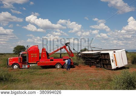 tow truck lifting an overturned bus on the roadside in the bush