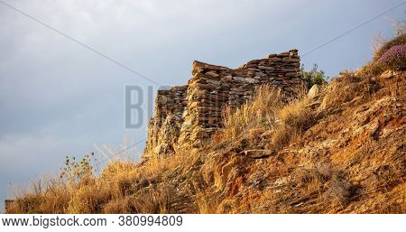 Fort Ruins At Tzia, Kea Island, Greece. Under View Of Red Stonewall Of Ancient Castle Background.
