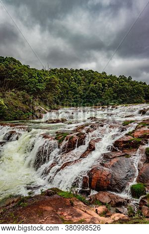 Waterfall With Red Rock And Green Lush Forest Flat Angle Shot