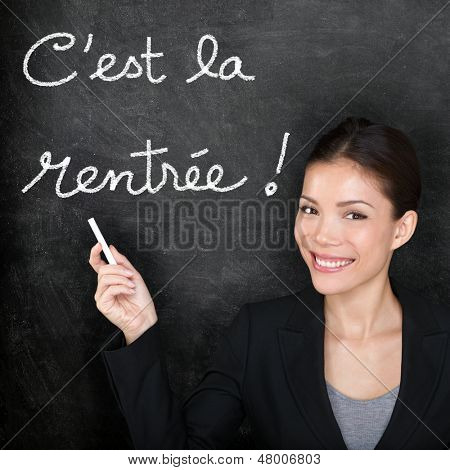 Cest la Rentree Scolaire - French teacher woman. Back to School written in French on blackboard. Female professor teaching French language at university, high shcool or primary school.