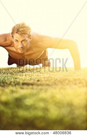 Push ups sport fitness man doing push-ups. Male athlete exercising push up outside in sunny sunshine. Fit shirtless male fitness model in exercise outdoors. Healthy lifestyle concept.