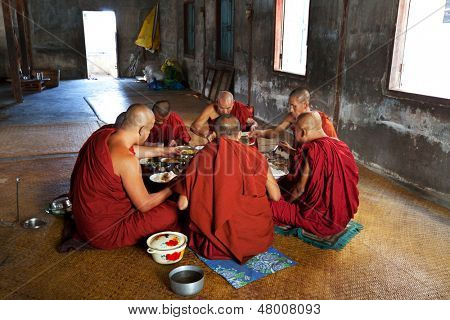 NYAUNGSHWE, MYANMAR - FEBRUARY 2: Buddhist monks have the scanty dinner in Shwe Yan Pyay on February 2, 2011 in Nyaungswe, Shan, Myanmar. The Buddhism is important part of social life in the Myanmar.