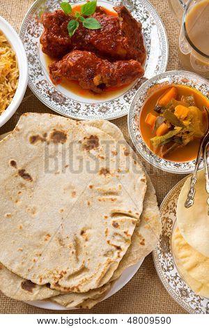 Chapatti roti, curry chicken, biryani rice, salad, masala milk tea and papadom. Indian food on dining table.