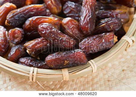 Dates fruit. Pile of fresh dried date fruits in a basket. poster