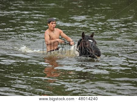 Boy bathes his horse
