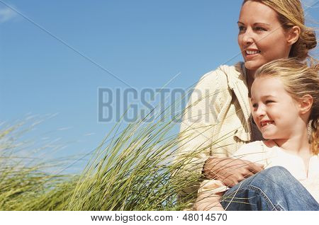 Happy mother and little daughter sitting in long grass against blue sky