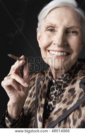 Closeup portrait of an elegant senior woman smoking cigarillo against black background
