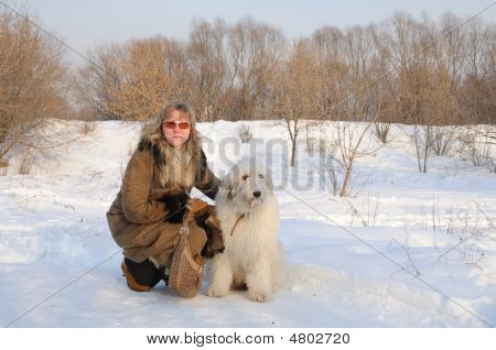 women and puppy south russian sheep dog in winter park poster