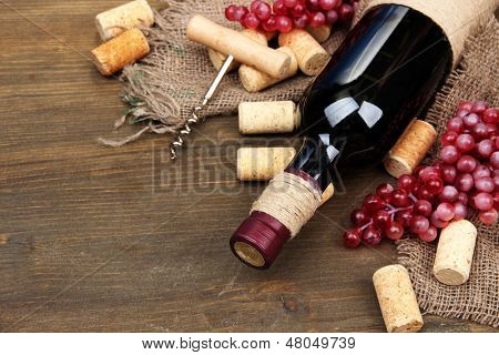 Bottle of wine, grapes and corks on wooden background
