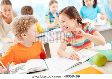 Portrait of two happy pupils interacting at drawing lesson