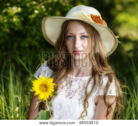 Woman In Park Seating On The Grass With Hat Over Her Head