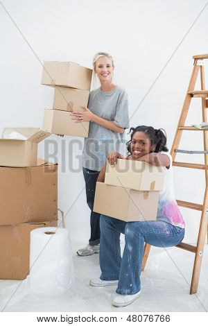 Housemates carrying cardboard moving boxes in their new home