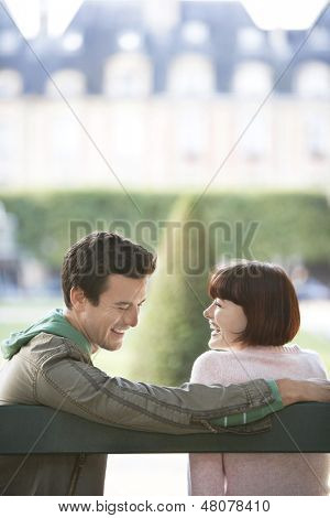 Happy young couple sitting on bench and laughing in park