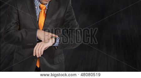 Businessman in black costume wind clock (wristwatch) on hand. ��¡lose up