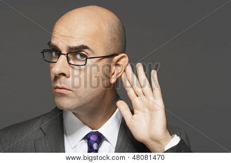 Closeup of a bald businessman with hand behind ear listening closely against gray background