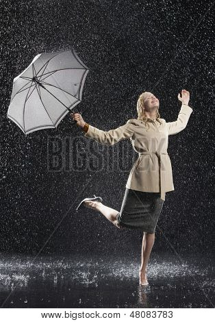 Full length of a young businesswoman in overcoat with umbrella enjoying the rain
