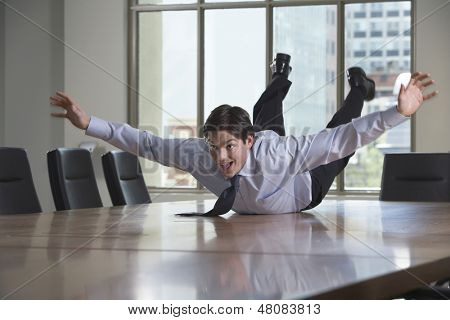 Young businessman sliding on stomach on conference table