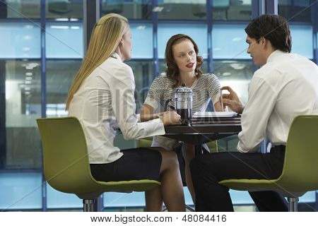 Three businesspeople taking a coffee break at work poster