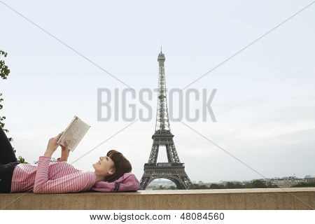 Side view of a young woman lying on balcony and reading book in front of Eiffel Tower
