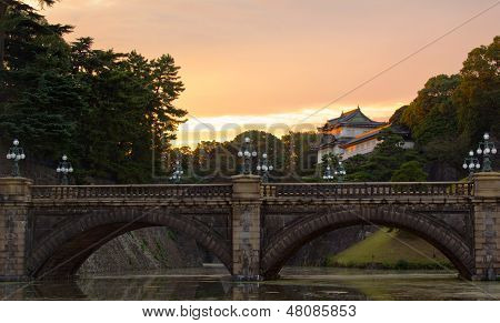 The stone bridge, called Meganebashi, an entrance to the inner grounds of the Tokyo Imperial Palace, at sunset. poster