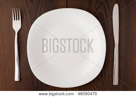 White empty plate, knife and fork served on table